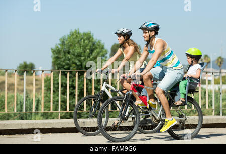Young smiling family with two little daughters traveling by bicycles. Focus on man - Stock Photo