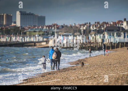 A family walk along the shoreline of Thorpe Bay beach in Southend on Sea, Essex, UK. - Stock Photo
