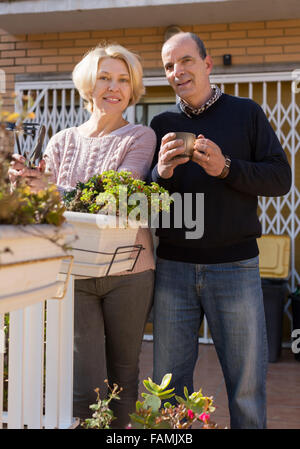 Happy smiling elderly woman with horticultural sundry and aged man drinking tea in patio - Stock Photo