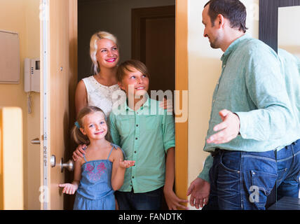 Hospitable smiling man greeting happy guests at apartment entrance - Stock Photo