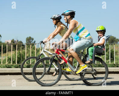 Happy active parents with two kids cycling on street road - Stock Photo