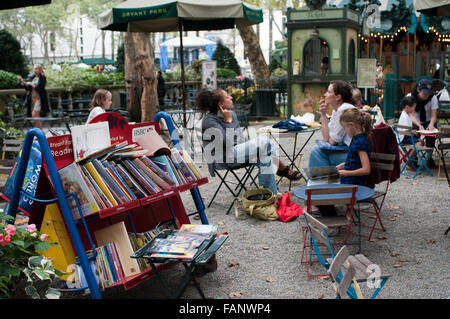Visitors browse the selection of books on carts at the Reading Room, an open air library in New York City's Bryant - Stock Photo