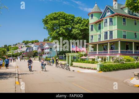 Tourists riding bikes on resort island of Mackinac Island Michigan - Stock Photo