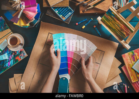 Designer workplace with creative tools and color swatches - Stock Photo