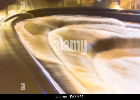 High water flow over Pulteney Weir in central Bath, Somerset, UK. A long exposure showing turbulence in the River - Stock Photo