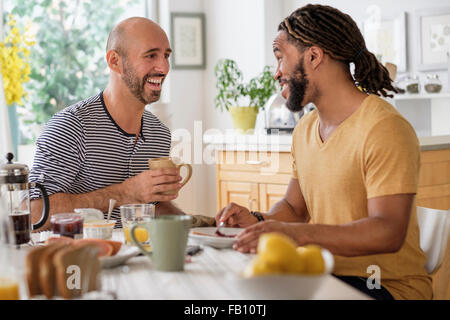 Smiley homosexual couple having breakfast in kitchen - Stock Photo