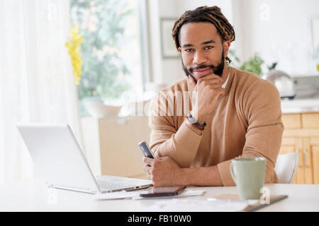 Portrait of young man with laptop at table - Stock Photo