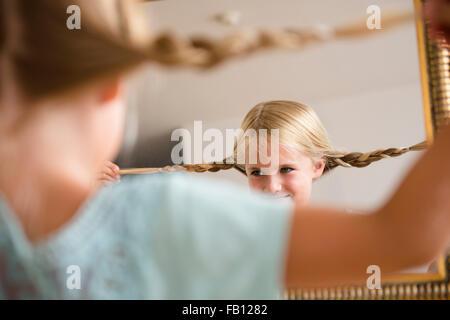 Girl (6-7) reflecting in mirror - Stock Photo