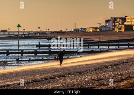 Unidentified Walking on Beach at Thorpe Bay, Essex in Strong Wind with Sand Blowing - Stock Photo