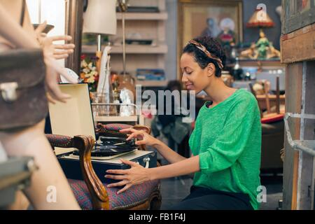 Young woman playing vinyl records in vintage shop - Stock Photo