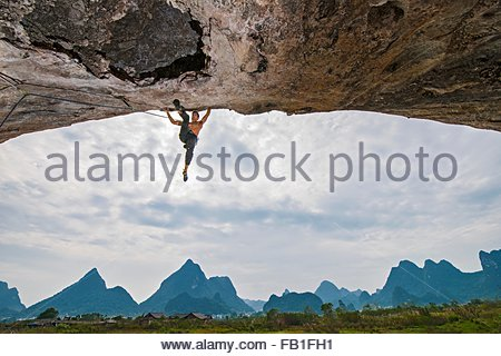 Scenic low angle view of rock climber hanging from arch of spicy noodle 5.14c, White Mountain, Yangshuo, Guangxi - Stock Photo