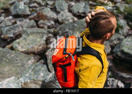 High angle view of mid adult man carrying orange colour backpack, Moraine lake, Banff National Park, Alberta Canada - Stock Photo