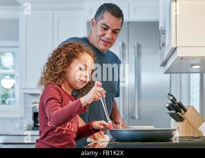 Father helping daughter cook on hob in kitchen - Stock Photo