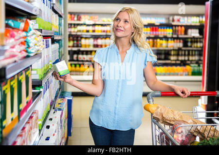Thoughtful woman holding product - Stock Photo