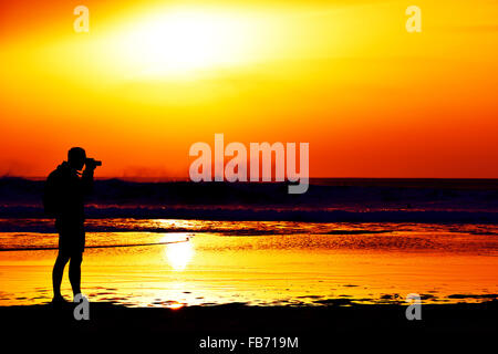 the silhouette of a young caucasian man taking a picture in front of the sea at dusk, against a colorful orange - Stock Photo