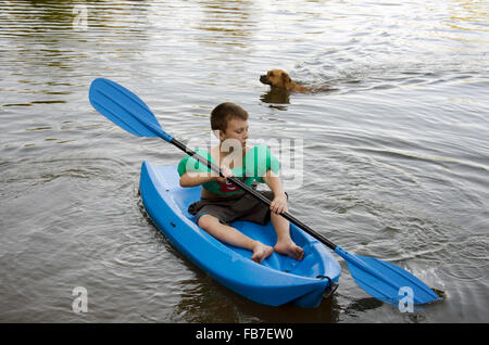 young boy in kayak and dog swimming behind him on pond or lake in summer - Stock Photo