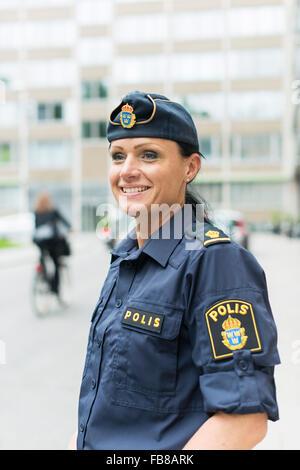 Sweden, Uppland, Stockholm, Policewoman smiling - Stock Photo