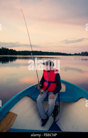 Sweden, Smaland, Tjust archipelago, Vastervik, Hasselo, Boy (10-11) fly fishing in boat on lake - Stock Photo