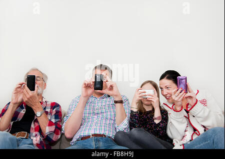 Girl (8-9) texting with family on sofa - Stock Photo