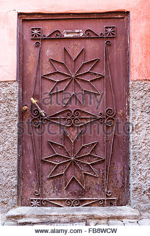 Metalwork door with star or flower shapes and flaking rusty red paintwork, against a rough red and grey plastered - Stock Photo