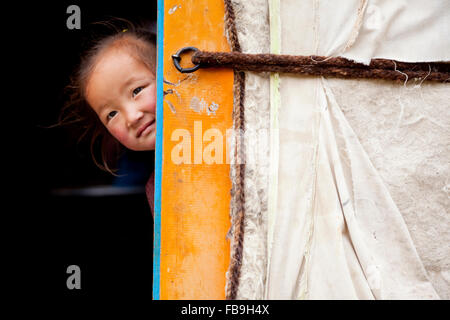 A cheeky young girl pokes her head out from inside her family's ger in Kharkhiraa Turgen National Park, Mongolia. - Stock Photo