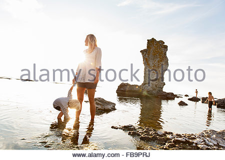 Sweden, Gotland, Faro, Mother with son (2-3) standing on rocky beach by sea - Stock Photo