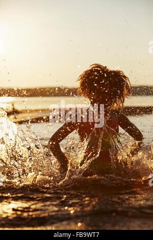 Sweden, Vastra Gotaland, Skagern, Girl (6-7) splashing in lake at sunset - Stock Photo