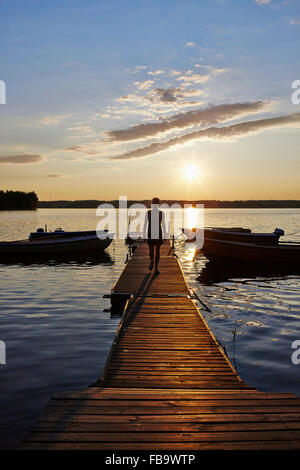 Sweden, Vastra Gotaland, Skagern, Woman walking on pier in lake at sunset - Stock Photo