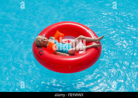 Greece, Karpathos, Amopi, Girl (6-7) lying in inflatable wheel - Stock Photo