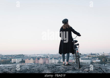 Sweden, Sodermanland, Stockholm, Sodermalm, Skinnarviksberget, Rear view of young woman standing by bicycle on rock - Stock Photo