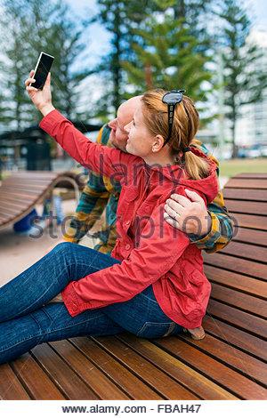 Australia, Queensland, Mid-adult couple taking selfie - Stock Photo