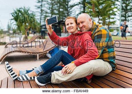 Australia, Queensland, Mid-adult couple taking selfie on bench in park - Stock Photo