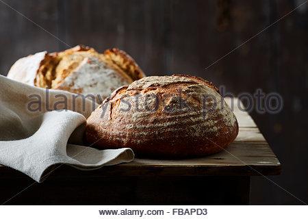 artisan baked bread on dark background - Stock Photo