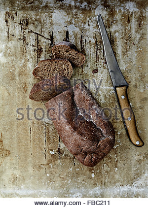 Sliced rye bread and rustic knife on old metal sheet - Stock Photo