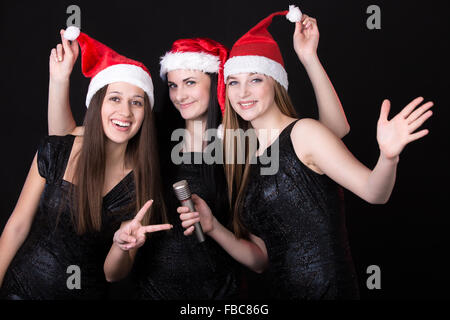 Group of three positive, happy smiling beautiful girls singers posing in cute red santa claus hats with microphone, - Stock Photo