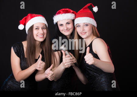 Group of three positive, happy smiling beautiful girls vocalists posing in cute red santa claus hats with microphone, - Stock Photo