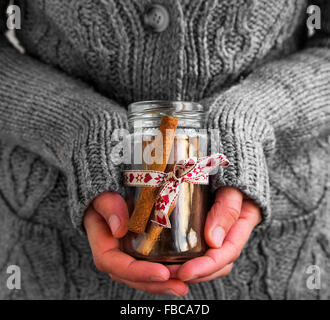 Decorated Jar with Cinnamon Sticks Holding by Female Hands - Stock Photo