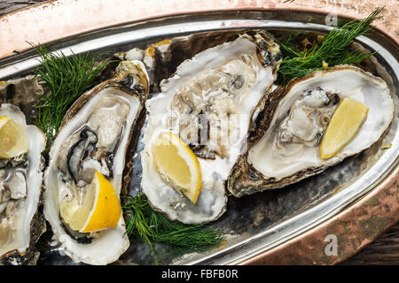 Opened oysters with piece of lemon on the cooper tray. - Stock Photo