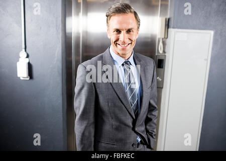 Smiling businessman standing front of elevator - Stock Photo