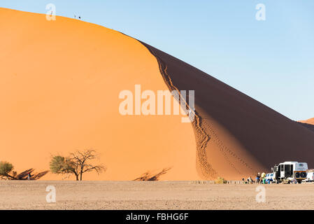 Tourists climbing sand dunes, Sossusvlei, Namib Desert, Namib-Naukluft Park, Hardap Region, Republic of Namibia - Stock Photo