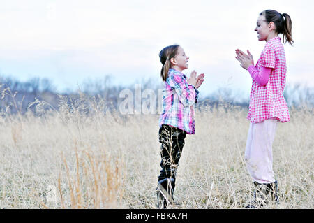girls playing clapping hand games in field - Stock Photo