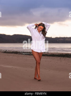 Beautiful young woman walking on the beach in white shirt and bare legs.  Model Release: Yes.  Property Release: - Stock Photo