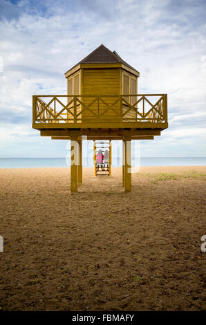 Two people sitting on steps of a lifeguard hut, Barbados, Caribbean - Stock Photo