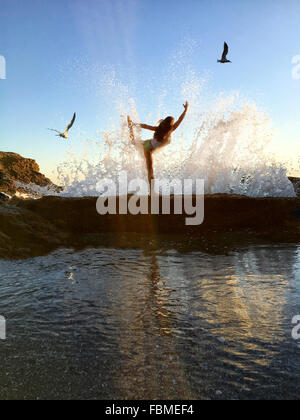Woman in still bow yoga pose on cliffs at beach - Stock Photo