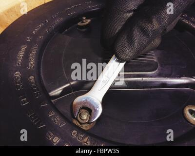 Cropped Image Of Hand Fixing Bolt With Wrench - Stock Photo