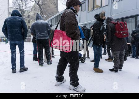 Refugees wait during heavy snowfall outside the Central Registration Office for Asylum Seekers of the State Office - Stock Photo