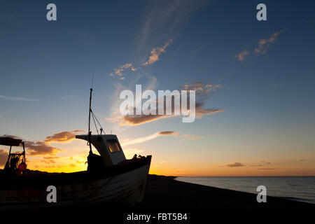 Sunset on the North Norfolk coast at Weybourne. Fishing Boat silhouette. - Stock Photo