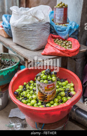 Plastic sacks, bags, bowls and tins of fresh green vegetables.  Large red bowl in foreground. Kohima Market, Nagaland, - Stock Photo