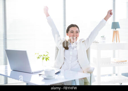 Businesswoman rejoicing with arms outstretched - Stock Photo