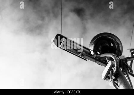 Close-up of a tall CCTV camera and street light in black and white set against a cloudy sky - Stock Photo